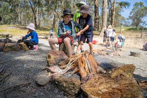 Children tending to campfire