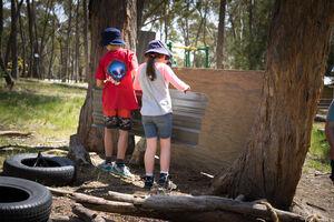 Two children working on hut building