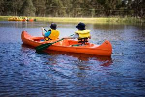 Boys padding in orange canoe