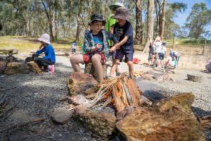 Students adding sticks to burning campfire