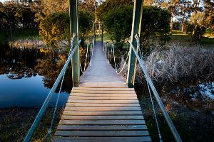 Wooden suspension bridge over dam
