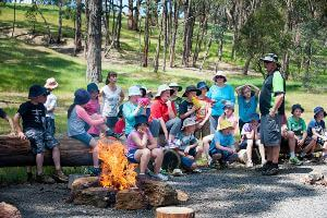 Students sitting around fire listening to activity instructor