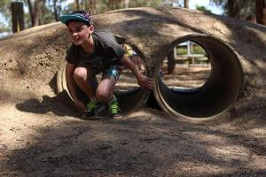 Boy crawling out of tunnel from the commando course