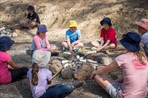 Students sitting around campfire cooking damper