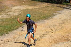 Student in activity harness running flying fox back up the hill.