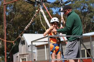 Boy giving thumbs up to camera as he prepares to go on the Giant Swing.