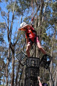 Harnessed student drops two crates off milk crate tower