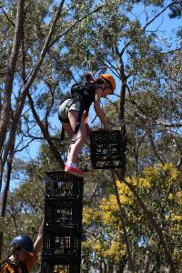 Harnessed student on milk crate tower placing extra crate on top