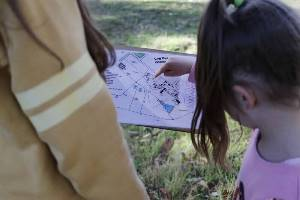 Girl pointing to orienteering map