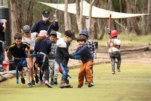 Kids running on possum glider pull team