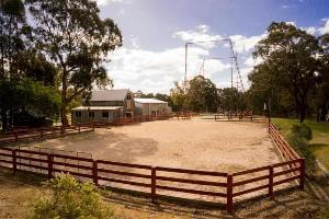 Sporting sand arena next to the barn and giant swing
