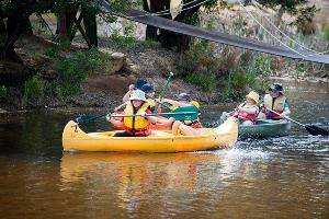 Group of students canoeing under bridge