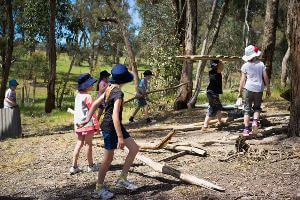 School students carrying logs for hut building