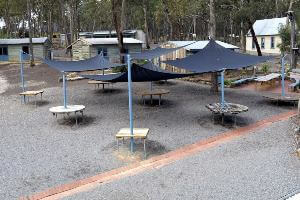 Outside meeting area with tables under shade sails