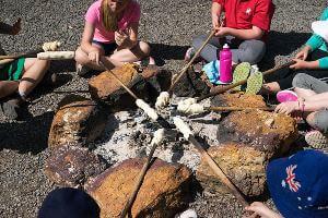 Students cooking damper around campfire