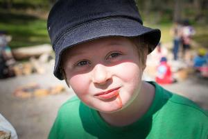 Boy with jam on chin from damper making
