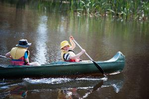 Two students padding in green canoe